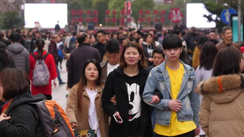 SHANGHAI - MARCH 18, 2018: Unidentified young friends at pedestrian Nanjing Road, medium telephoto shot of passers. Many people seen on background, popular shopping and ramble area at Chinese city