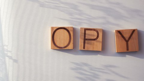 "The word ""COPY"" is laid out in wooden letters"