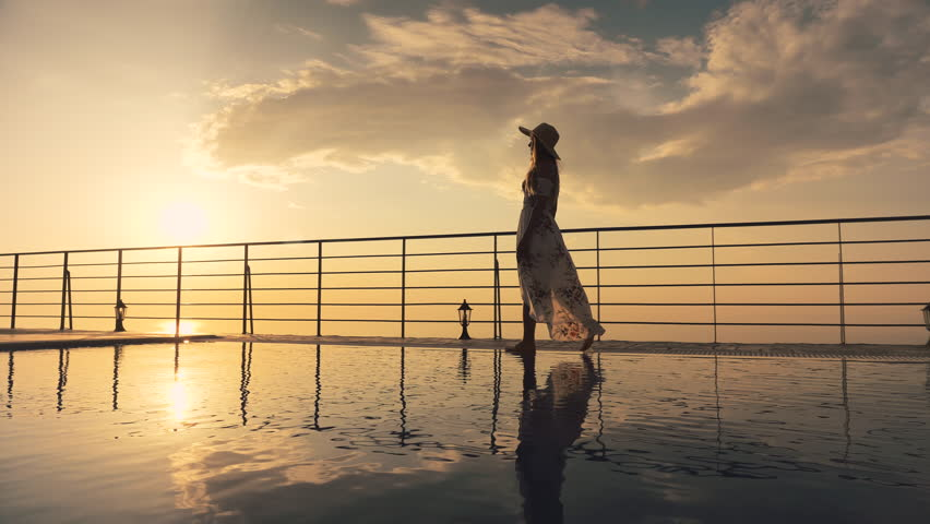 Slow motion - Beautiful shot of a woman in a long flow dress walking by the poolside and splashing water with her foot at colorful sunset. Girl leaning on the railing to enjoy the view at end of clip
