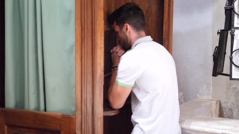 Young man sitting and kneeling in church confessing sins to pastor inside a confessional