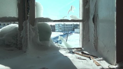 View of airplane monument to aviators through frozen broken window. MiG-19 aircraft in honor of the pioneers and defenders of the sky of Chukotka. Way to ghost town Gudym. Unique place for stalkers.