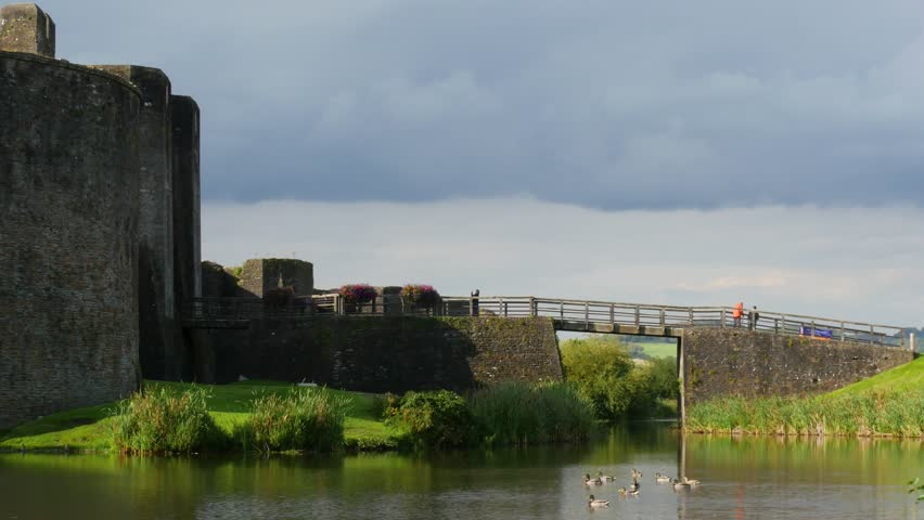 Tourists enjoy visiting Caerphilly Castle and the historic site while ducks swim in the moat.