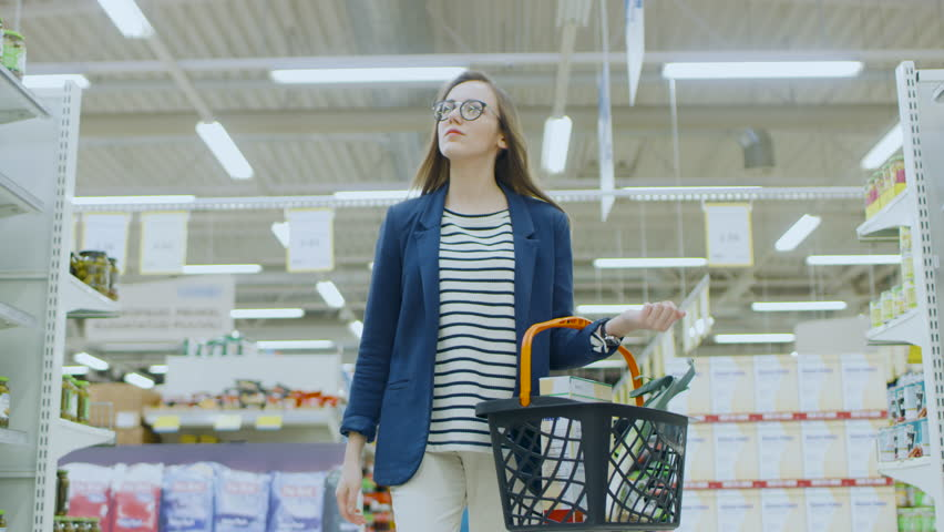 At the Supermarket: Beautiful Young woman with Shopping Basket Walks Through Canned Goods Section, Browsing. Big Store with Lots of Aisles. Shot on RED EPIC-W 8K Helium Cinema Camera. | Shutterstock HD Video #1015782337