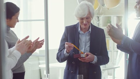 Medium shot of happy old woman opening present from colleagues and saying thank you during retirement party in office