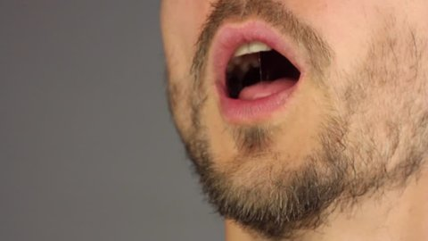 bearded man opens his mouth, sneezes, wipes his nose with his hand, side view, closeup macro