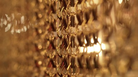 Slow, smooth movement of long gold chains. Uniform swing. Gold background for relaxation. Meditation. Relax. Texture for soothing. Glitter. Vertical picture. Blurred