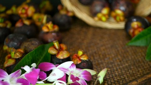 Top view of fresh delicious harvested mangosteens on wooden table. Thai organic purple fruit in the basket. Exotic natural blurred background with tropical flower. Healthy food and eating concept.