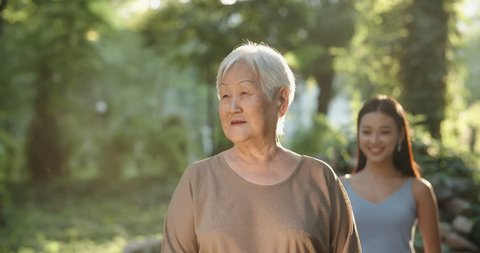 Cheerful panasian granddaughter approaching her mature grandmother, closing her eyes, then hugging and kissing her 4k