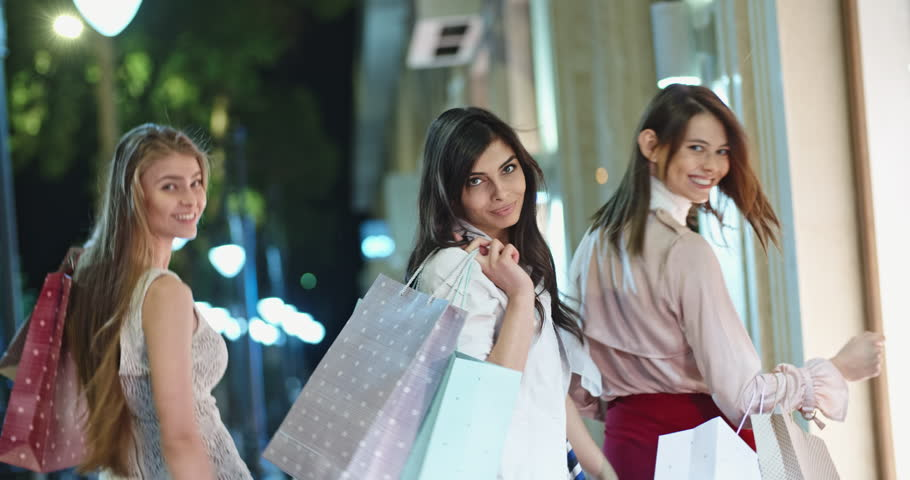 Backview of three female friends walking near mall with shopping bags in hands, turning and looking at camera 4k