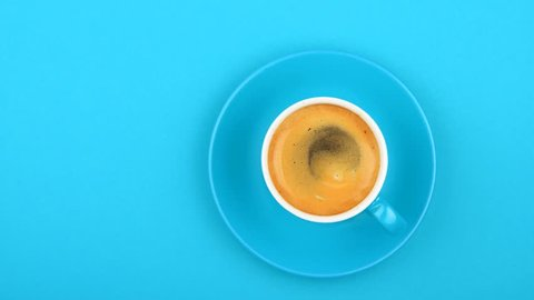 Close up one full white cup of espresso coffee and saucer over pastel blue paper background with slow motion animated spin of coffee froth, elevated top view, directly above