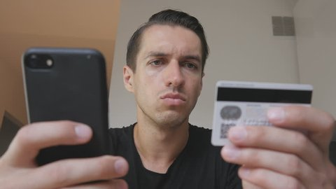 Angry young man buying online uses a phone and a credit card and feeling that he was deceived. Unsuccessful Internet shopping. Credit card fraud