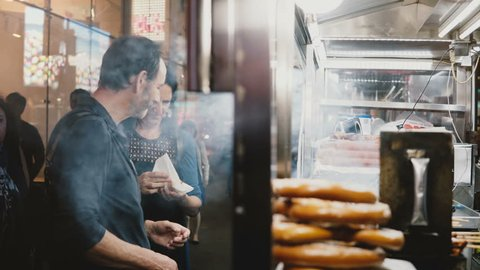 NEW YORK AUG 18 2017 - Caucasian adult couple standing near a street food vendor buying snacks in evening New York City.