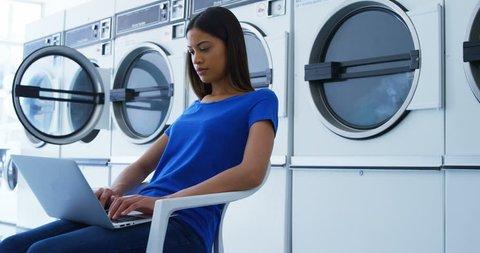 Attentive woman using laptop at laundromat 4k