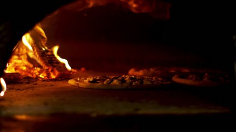 Italian Pizza cooking in the oven with wood fire
