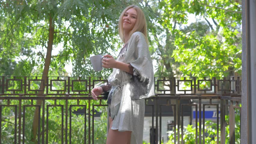 good morning, attractive girl in sleepwear enjoys fresh air on the balcony with a cup in her hands and then goes to the camera and smiles
