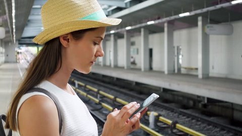 Young woman in white shirt on overground subway station. Female tourist using mobile phone at train station. Teenage girl texting on smartphone while waiting for train