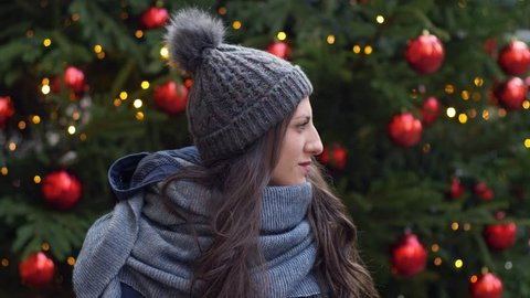 Young woman looking around and smiling at camera- Christmas Time