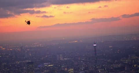 Stunning shot following London's rescue helicopter with beautiful sunset above London City. BT Tower, clouds, and city lights in the background.