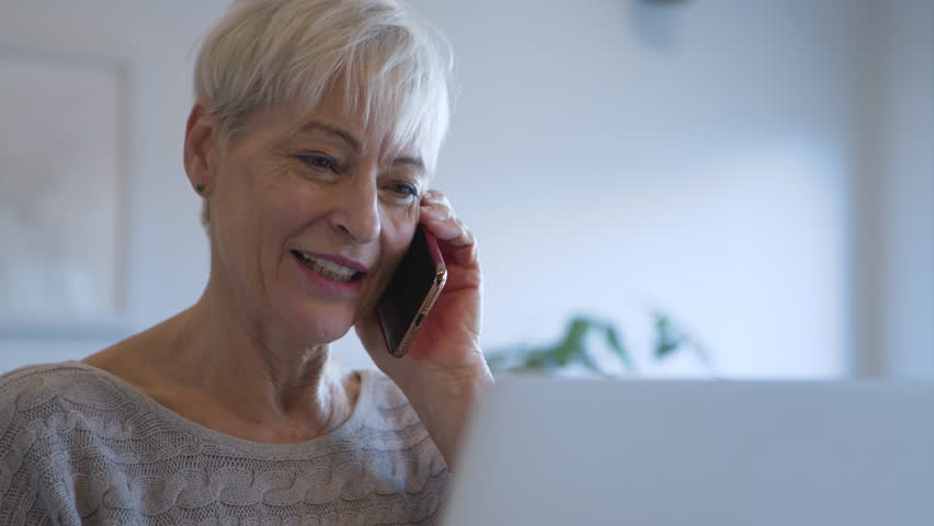 Dolly shot of happy senior woman talking on smart phone at home