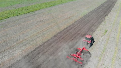 Tractor plowing fields, preparing land for sowing. Aerial view. Farmer in tractor preparing land  in farmlands. Tractor plows a field. Agriculture industry, cultivation of land