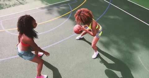Overhead shot of young adult females playing basketball