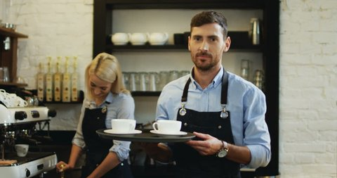 Portrait shot of the handsome Caucasian barmen holding cups of coffee and going to the bar while his female co-worker preparing more behind at the coffee machine.