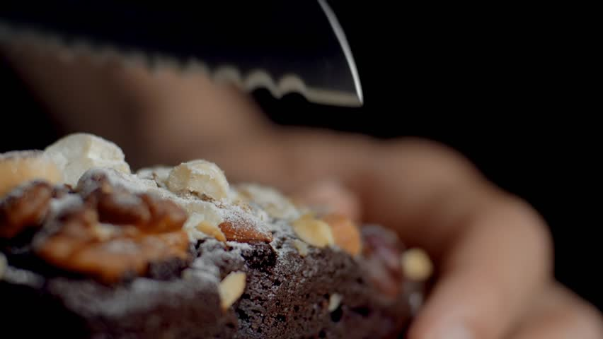 Cutting brownie with nuts. Brownie cuts falling. Slow motion.