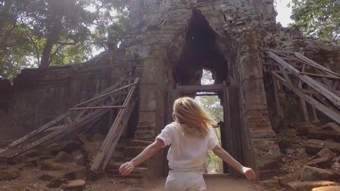 Slow motion of young woman running into temples gate in Cambodia happy to discover new places enjoying Asia travel fun concept