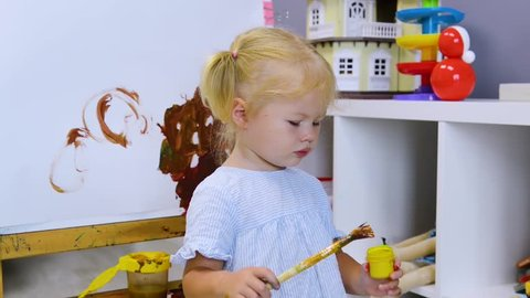 Happy baby girl with tassel in the paint painting at home or kindergarten