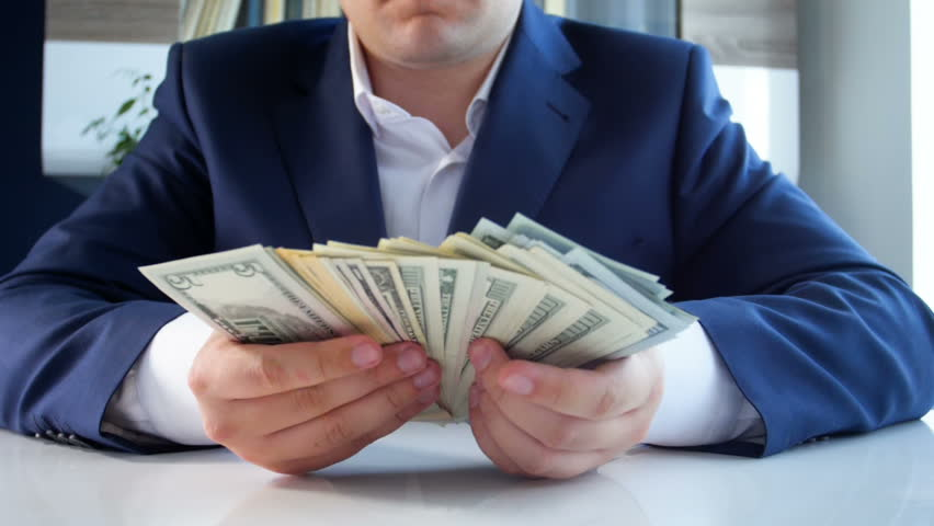 Slow motion video of businessman sitting in office and counting big stack of US dollars #1016086447