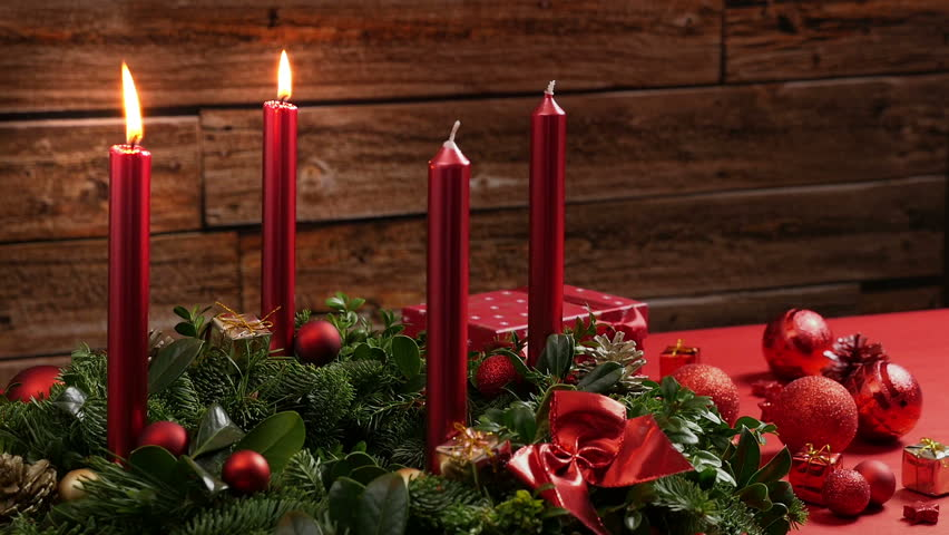 Two burning red candles on a traditional advent wreath of green fir twigs and mistletoes with festive decoration in front of a rustic wooden wall, close-up real time shot with copy space, nobody