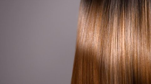 Hair. Beautiful healthy long smooth flowing brown hair close-up texture. Dyed straight shiny hair background, coloring, extensions, cure, treatment concept. Haircare. Slow motion 4K UHD video