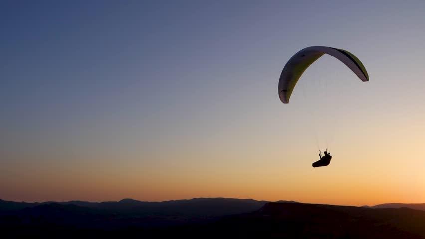 Paraglider pilot makes steep maneuver at background of Kara-Dag mountain, turning around 180 degrees.