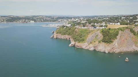 Aerial view of the coastal town and harbour of Torquay England. Coastline and beach front is visible in the distance.