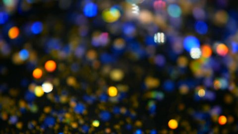 Defocused shimmering multicolored glitter confetti, black background. Rainbow colors, sparkle circles. Holiday abstract festive texture of shiny blurred bokeh light spots.