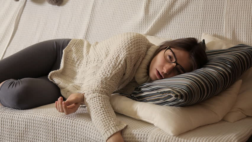 A young girl in a winter evening at home in a white sweater on the couch with glasses watching TV and falling asleep. Evening. House. Comfort. Heat. Winter | Shutterstock HD Video #1016204827