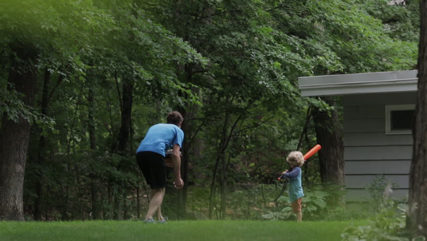 Cheerful boy playing baseball with father at yard | Shutterstock HD Video #1016209147