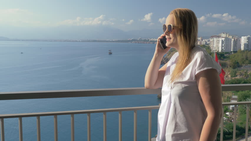 Young woman talking on mobile phone and looking at the sea from balcony. Antalya, Turkey