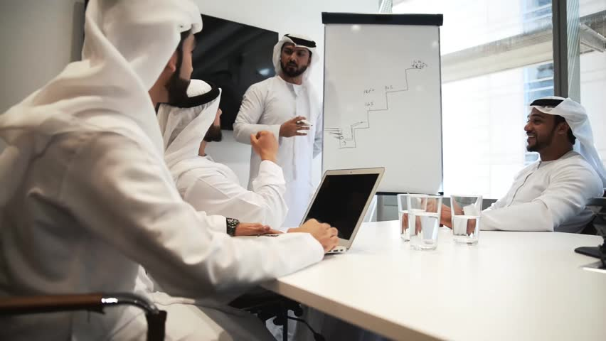 Four businessmen in dubai working in their office, planning the future development of the company