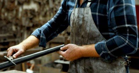 Blacksmith measuring metal rod with caliper in workshop 4k