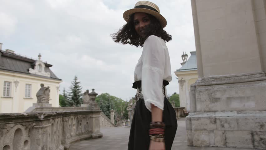 Back view of attractive curly young woman in trendy dress and straw hat walking through the old palace, spinning around, and smiling to camera. Cheerful mood, positive emotions. Model, shooting | Shutterstock HD Video #1016238127