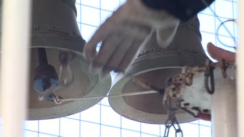 The man is ringing big and small bells in the church. Undefined location. Just his hands. Video with sound.