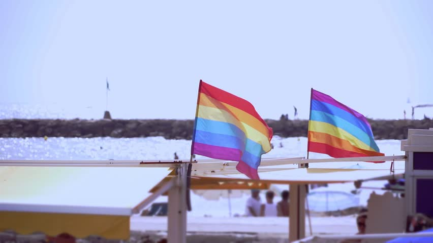 Slow motion gay pride flag blowing in the wind on Sitges, in Barcelona province. Perhaps Spain top gay destination, with LGTB events like Gay carnival, pride and Gay Spring break. Slowmotion from 120  | Shutterstock HD Video #1016257687
