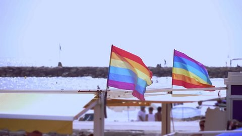 Slow motion gay pride flag blowing in the wind on Sitges, in Barcelona province. Perhaps Spain top gay destination, with LGTB events like Gay carnival, pride and Gay Spring break. Slowmotion from 120
