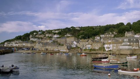 Pan across the pretty harbour of Mousehole in Cornwall with colorful fishing boats moored