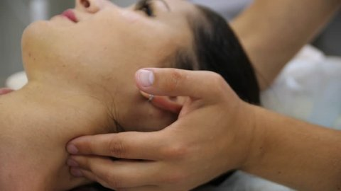Woman doing neck massage at the reception of the chiropractor. Men's hands do massage of the cervical spine to an attractive girl. Massaging pain points