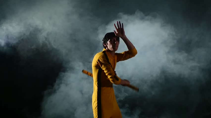 The man in  yellow suit practicing kung fu. Master holding nunchuck. Fighter isolated on black background. Concept of healthy life and martial arts. smoke, Slow motion #10162697