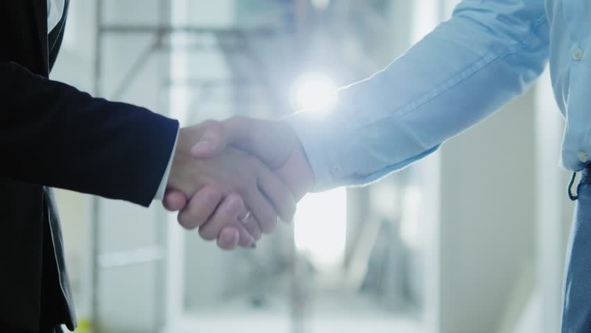 Two business partners shake their hands | Shutterstock HD Video #1016282317