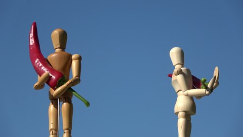 Rotating two wooden artist  manikin mannequin on sky background and holding red hot chili peppers