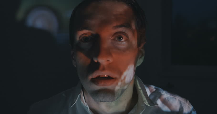 Close up of young man watching a horror video or film on TV or a computer monitor at home. He looks scared